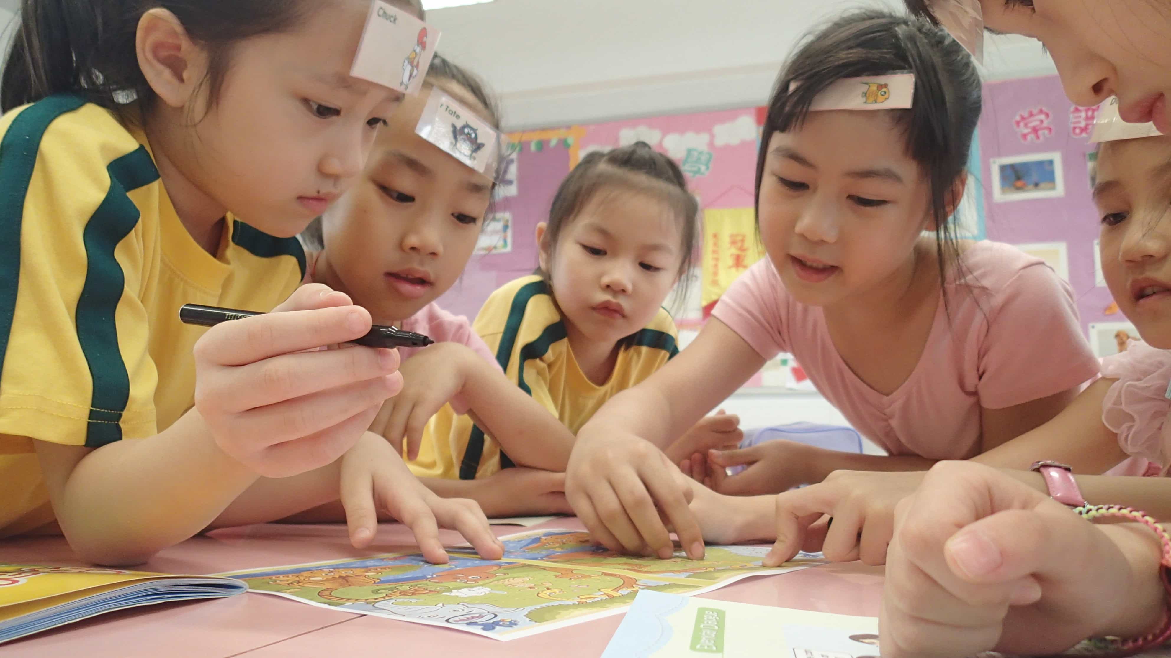 asian school girls are playing a table game in a TEFL classrom